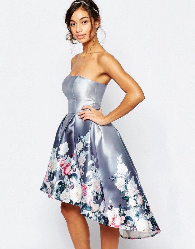 Meisje in een bandeau-cocktailjurk met een asymmetrische volle rok