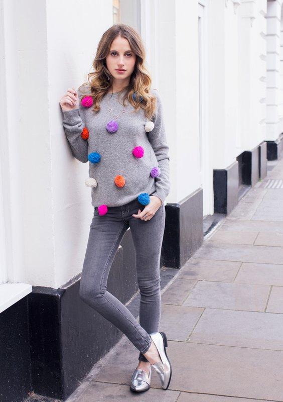 Meisje in een trui met veelkleurige pompons