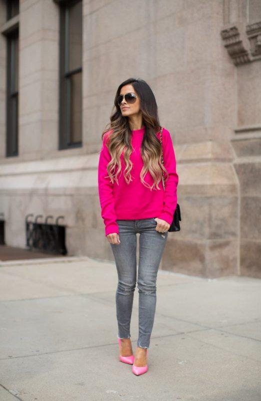 Meisje in een felroze trui en een skinny jeans