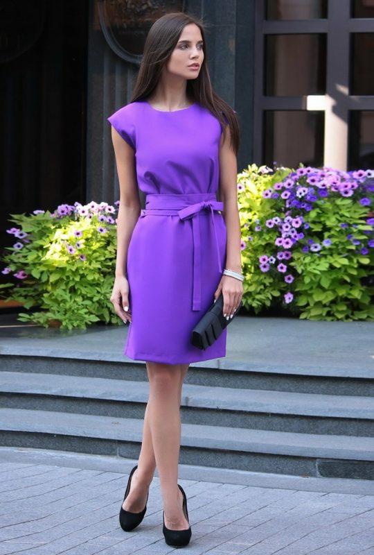 Meisje in een paarse cocktailjurk met een strik