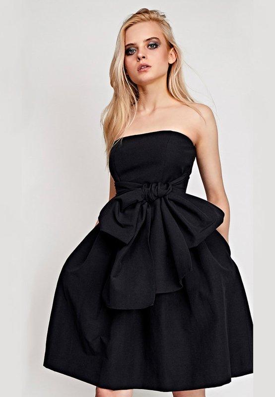 Meisje in een zwarte cocktail bandeau jurk met een volle rok
