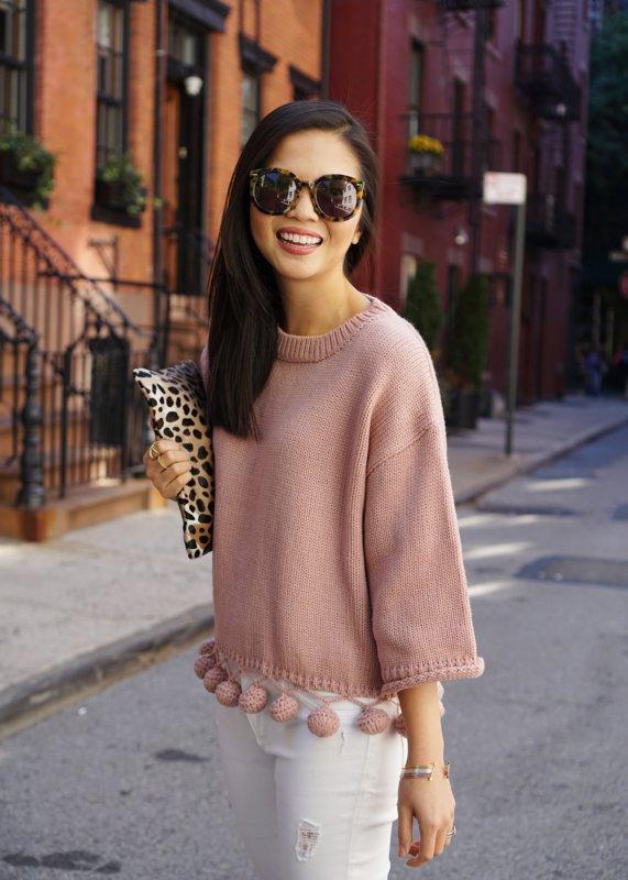 Meisje in een trui met pompons aan de zoom