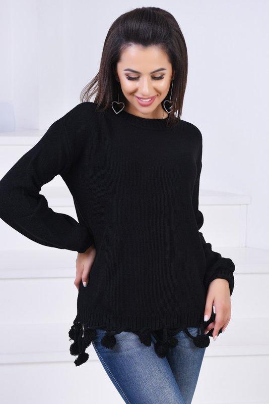 Meisje in een zwarte trui met pompons aan de zoom