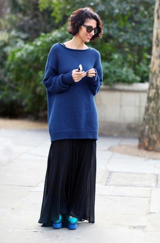 Meisje in een sweaterjurk met een rok op de vloer