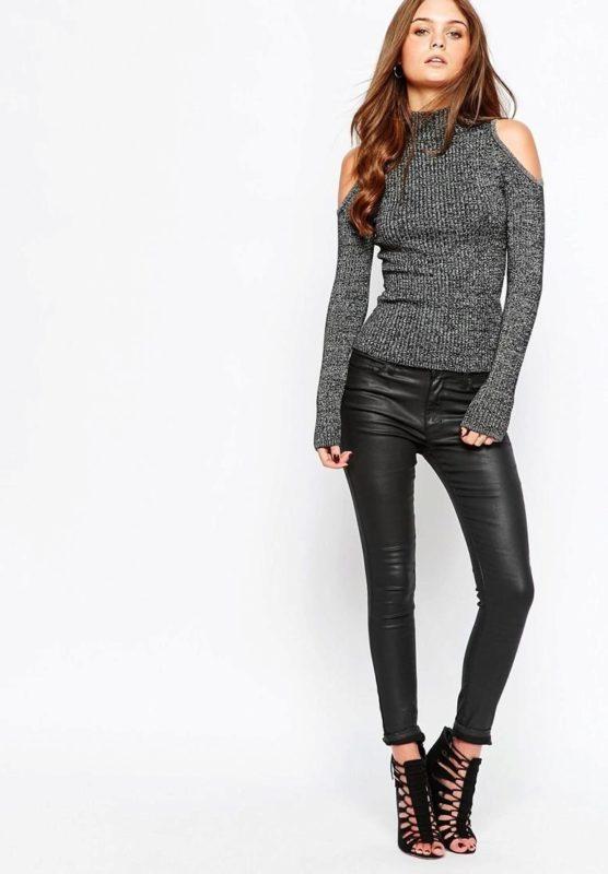 Meisje in een trui met uitsparingen op de schouders en lederen legging.