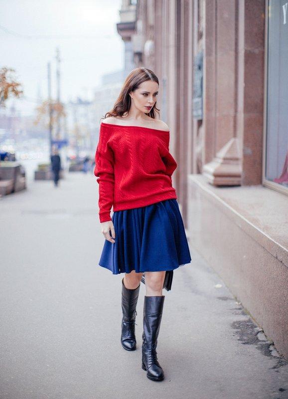 Meisje in een trui met blote schouders en een rok.