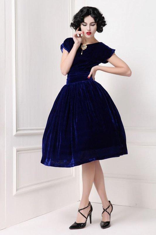 Meisje in een donkerblauwe fluwelen cocktailjurk