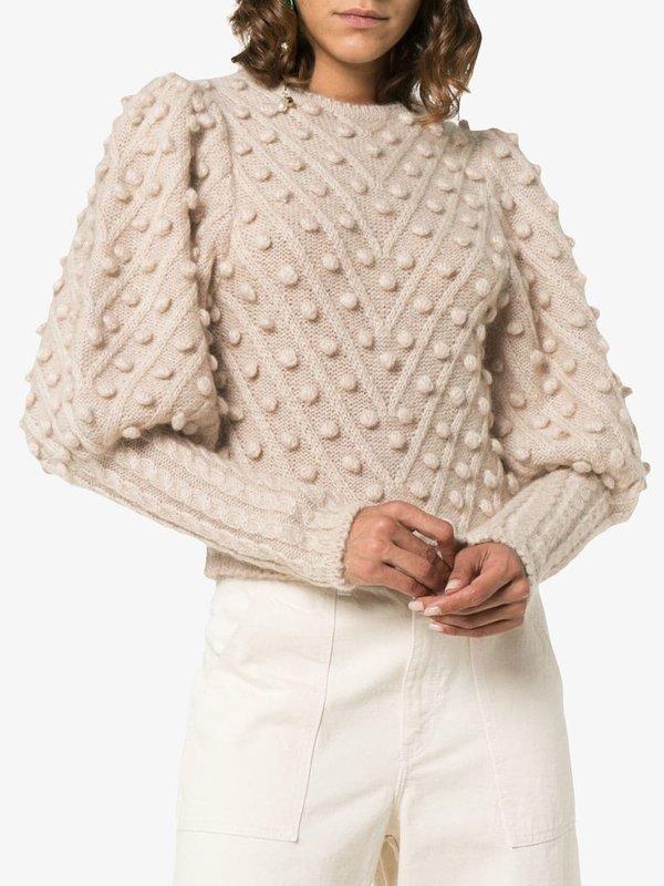 Meisje in een beige trui met pompons.