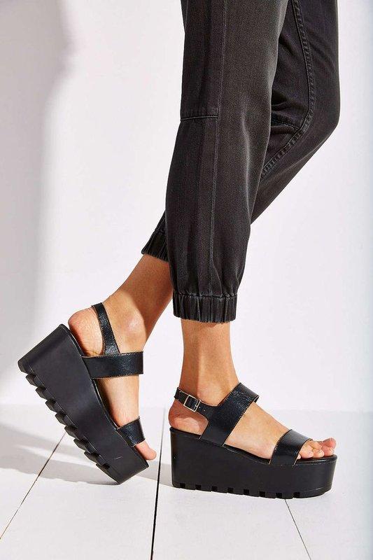 Meisje in sandalen op een hoog ononderbroken platform