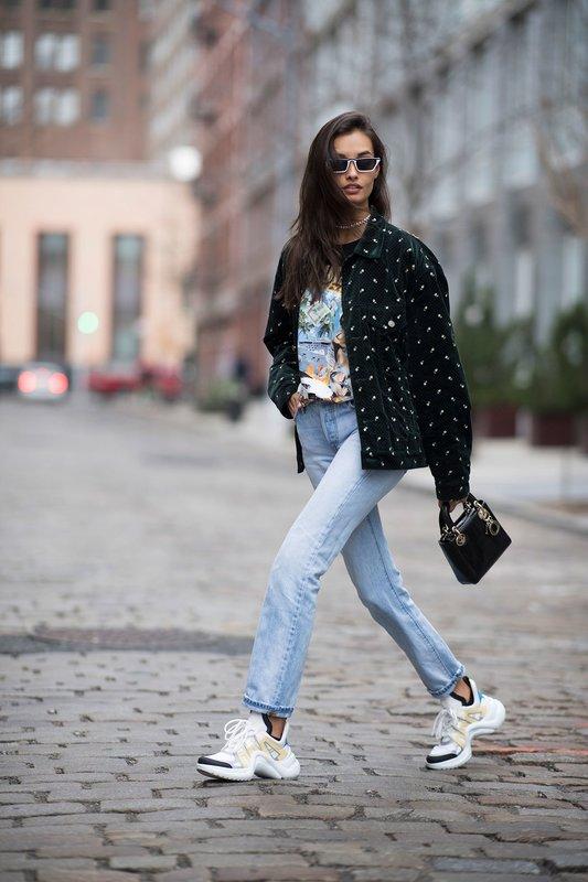 Een meisje in dikke sneakers gecombineerd met jeans