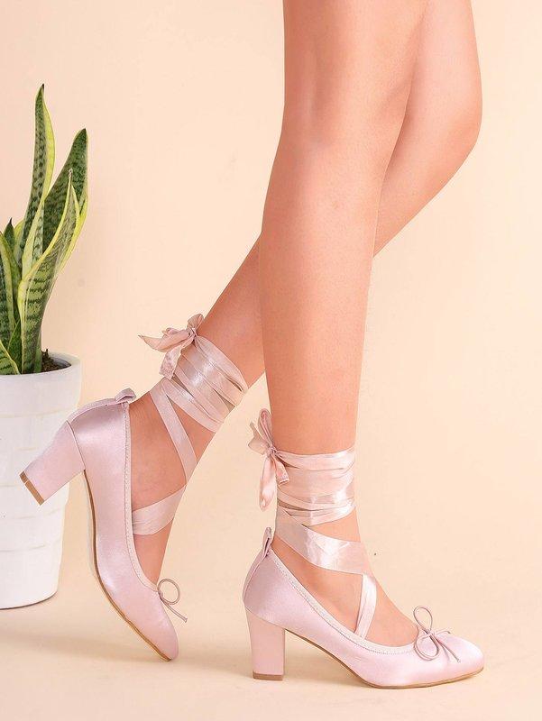 Meisje in schoenen met satijnen linten.