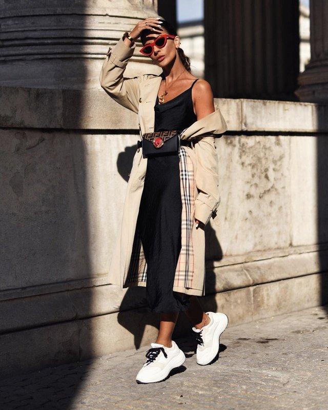 Een meisje in dikke sneakers gecombineerd met een jurk