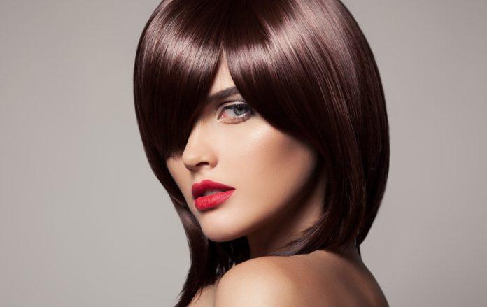Mergaitė su madingu kirpimu ant vidutinių plaukų