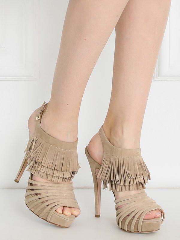 Meisje in schoenen met hoge hakken met een franje.