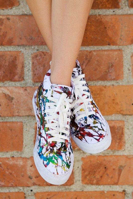 Meisje in sneakers met artistieke schilderkunst