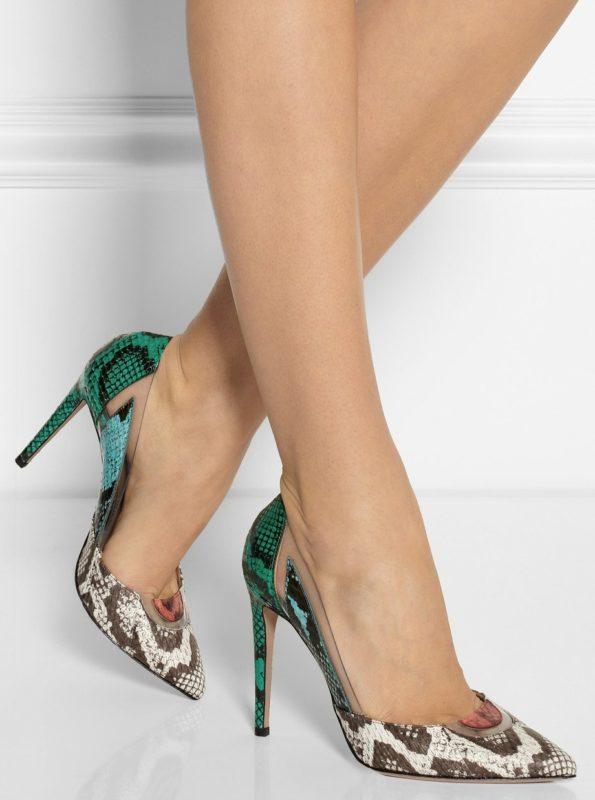 Meisje in schoenen met imitatie onder de huid van een slang