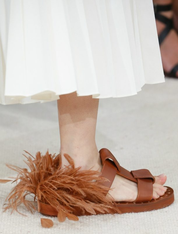 Meisje in sandalen met veren in de rug