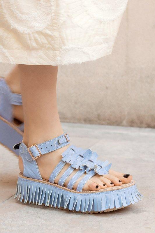 Meisje in sandalen met een franje langs de rand van de zool