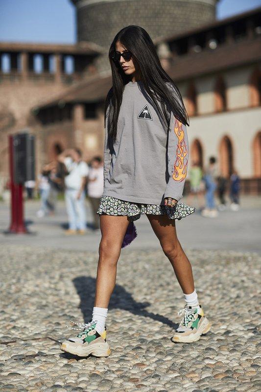 Een meisje in dikke sneakers gecombineerd met een rok