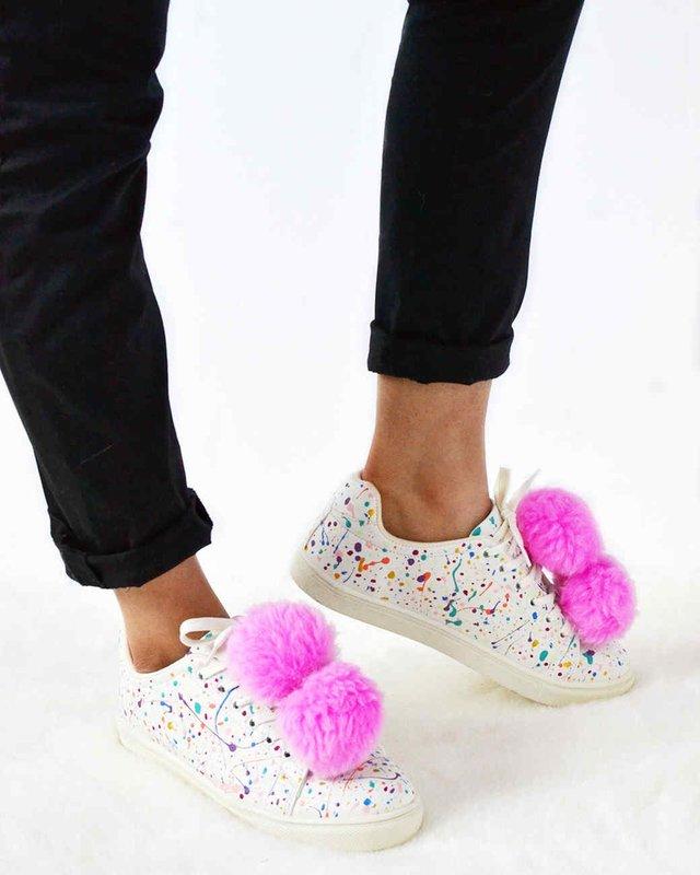 Meisje in sneakers met pompons.