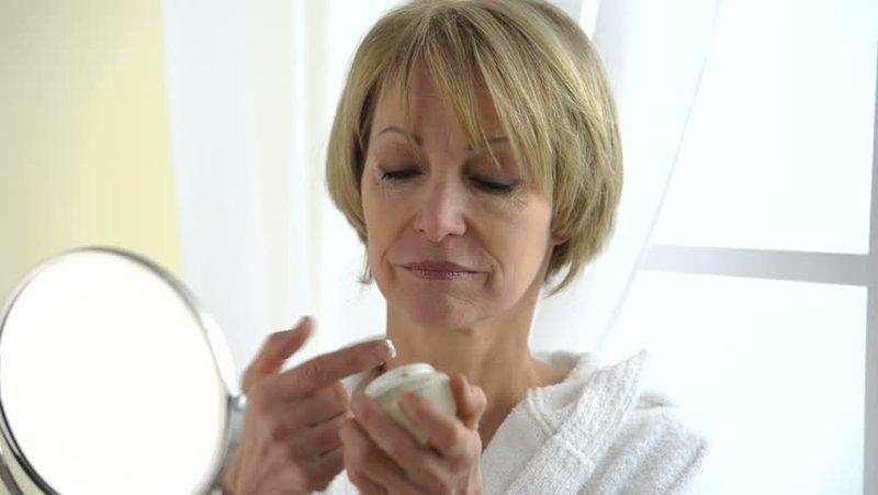 Vrouw na 50 hydrateert haar gezicht