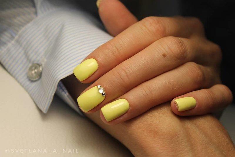 Manucure jaune délicate avec des strass.