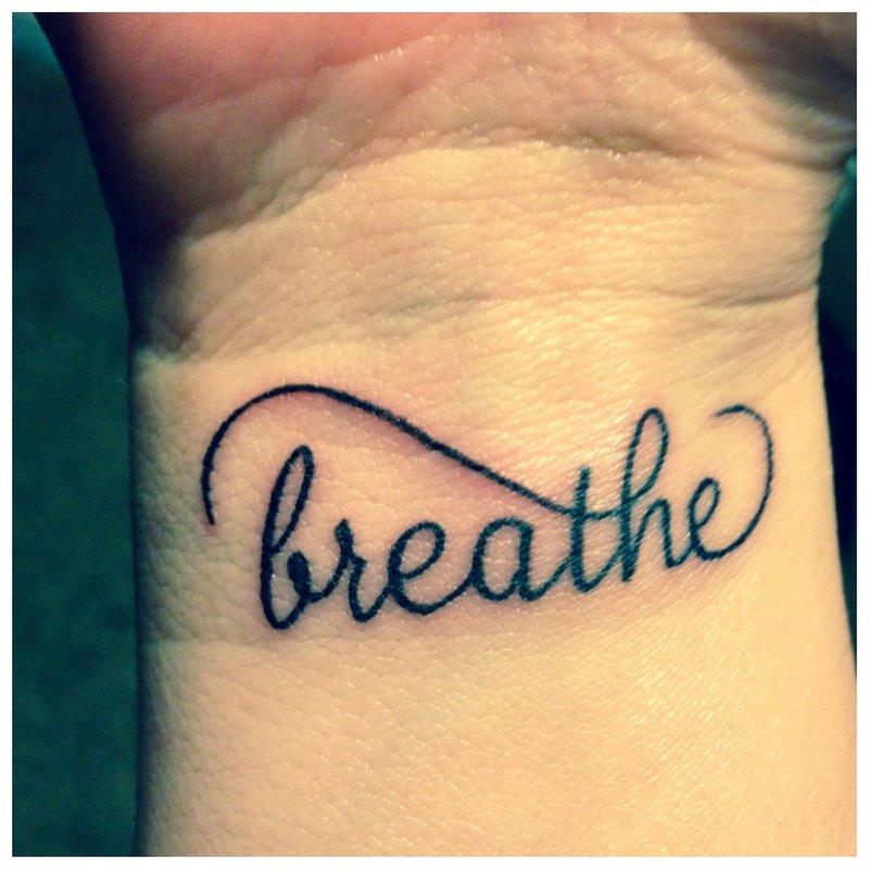 Kvėpuok - užrašas ant tatuiruotės ant riešo