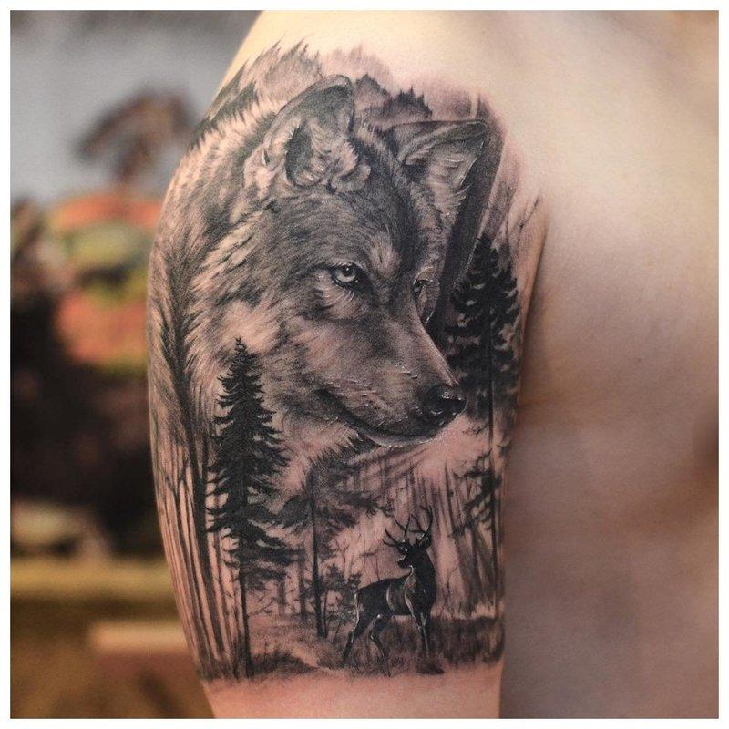 Wolf in het bos - tatoeage op de schouder van een man