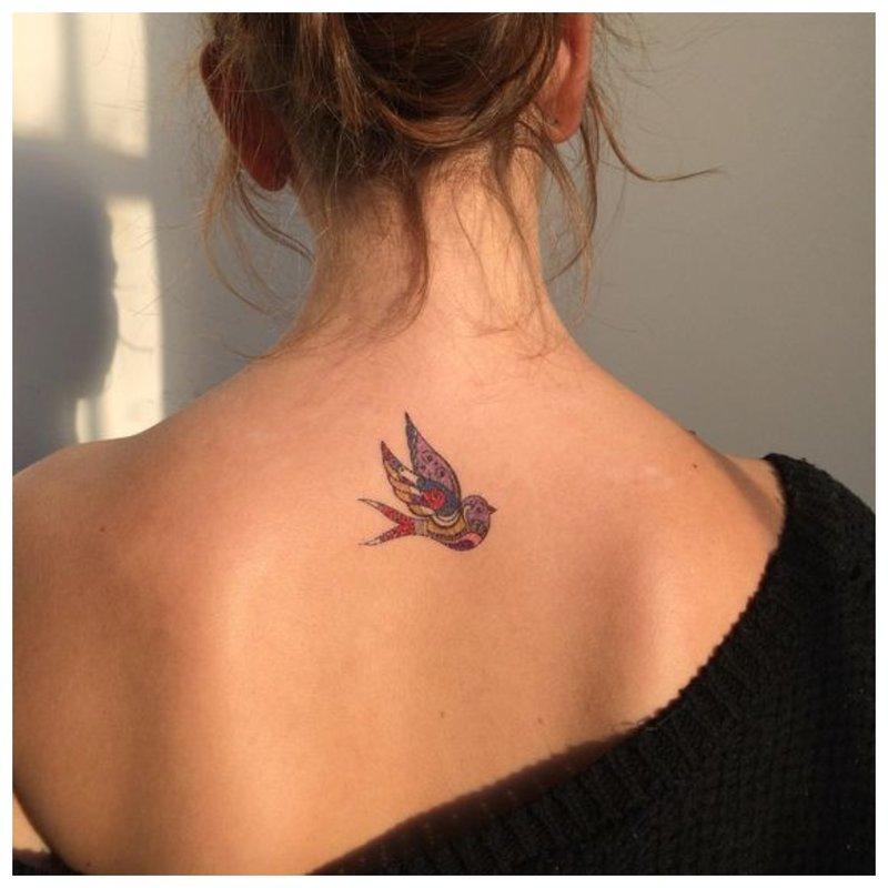 Paukštis - tatuiruotė ant merginos nugaros