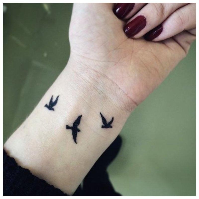 Tatuiruotė paukščių pavidalu ant mergaitės rankos
