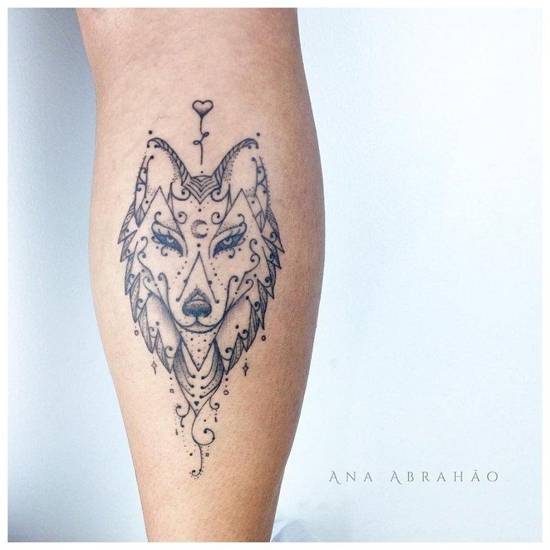 Originele tatoeage van een wolf op het kalf van een man