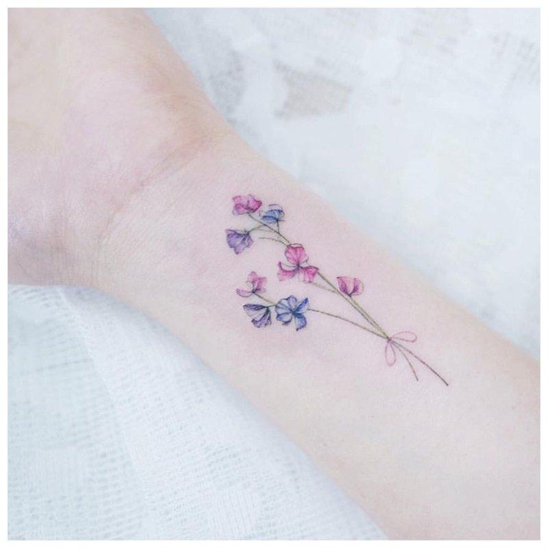 Maža gėlė ant rankos - tatuiruotė