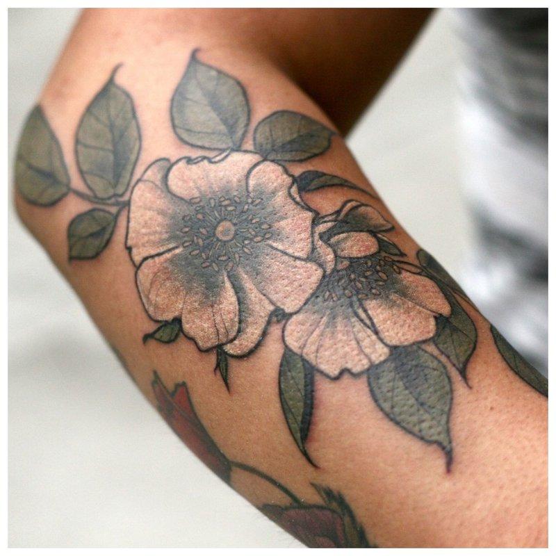 Didelė gėlių tatuiruotė ant mergaitės rankos