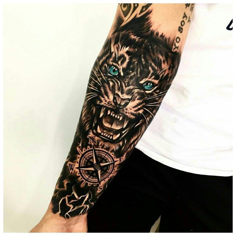 Piktas liūtas - tatuiruotė ant vyro dilbio