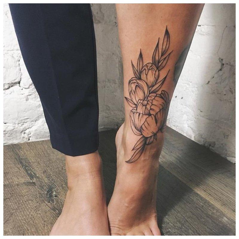 Kontūrinė gėlių tatuiruotė ant blauzdos