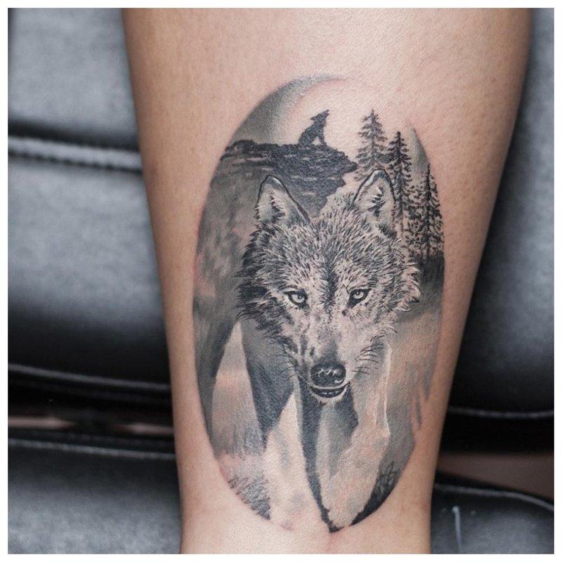 Wolf-tatoeages op het kalf van een man