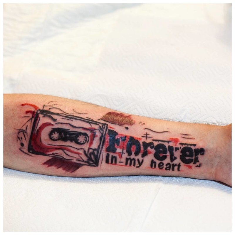 Ryškus tatuiruotės užrašas ant rankos.