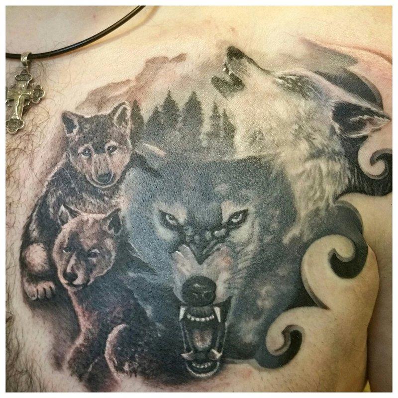 Wolf met zijn roedel - tatoeage op de borst van een man