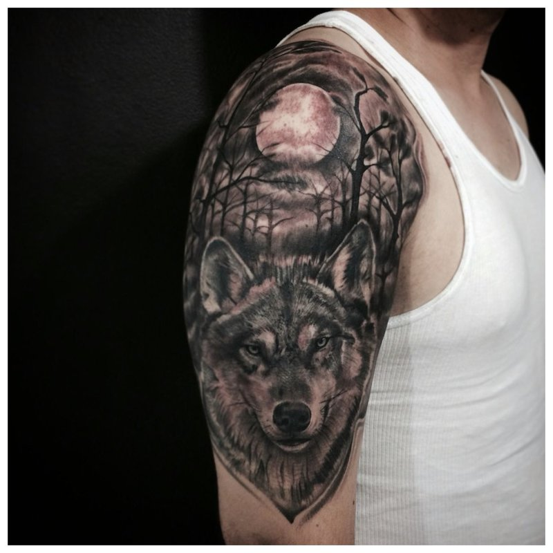Wolf in het bos - tatoeage op de schouder