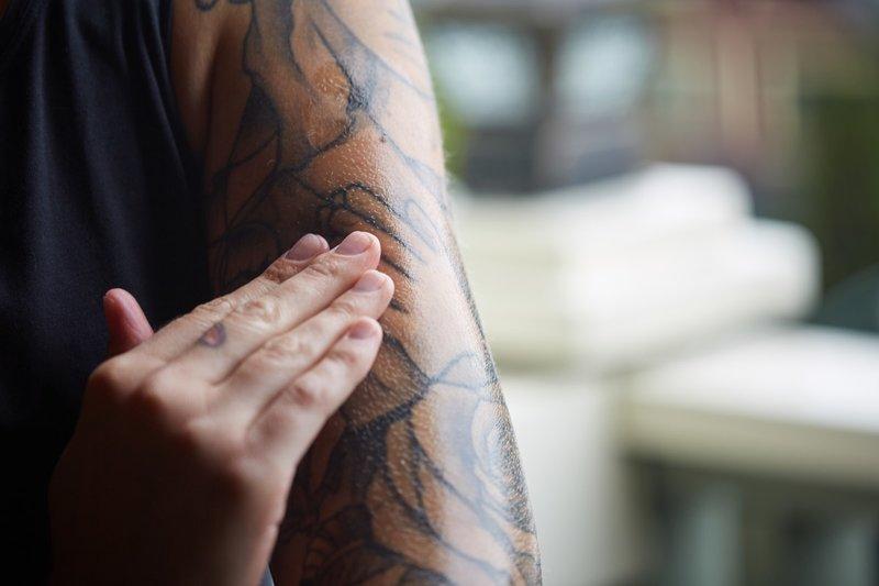 Meisje smeert een tatoeage met zalf