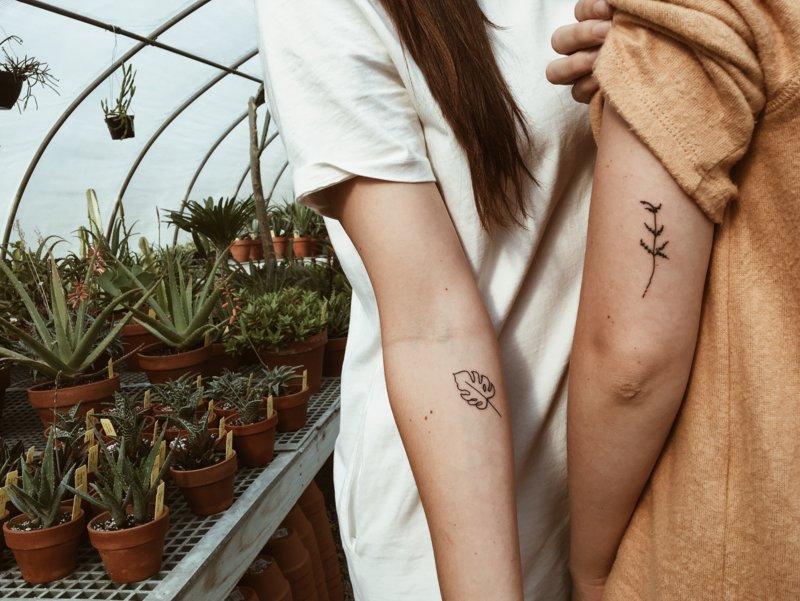Pora su tatuiruotėmis ant rankos.
