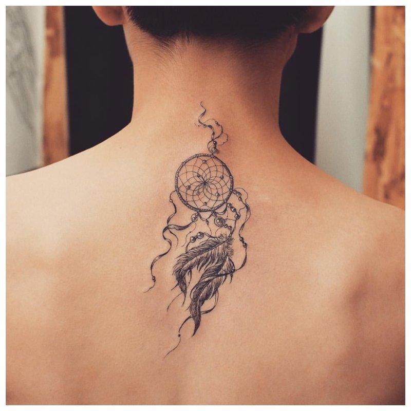 Tatuiruotės amuletas ant merginos nugaros