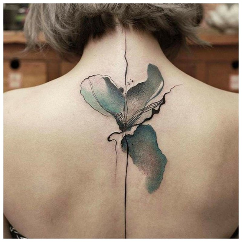 Akvarelės tatuiruotė gėlės pavidalu tarp menčių