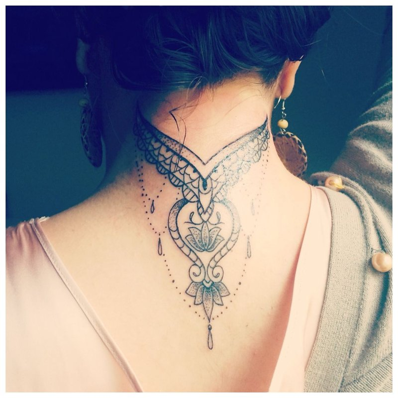 Tatuiruotė ant merginos nugaros ir kaklo