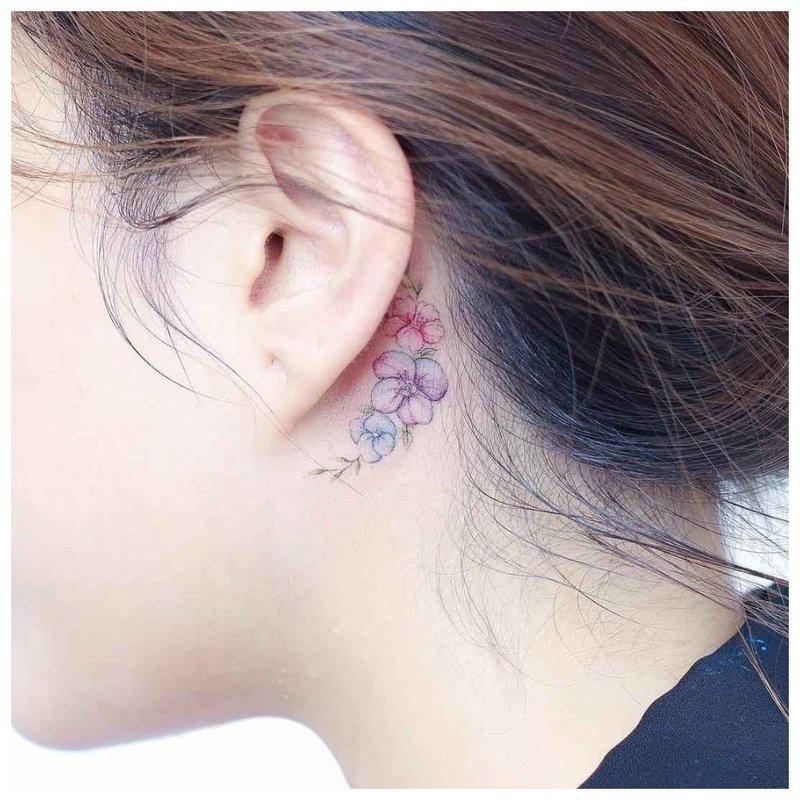 Subtilus gėlių tatuiruotė ant mergaitės kaklo