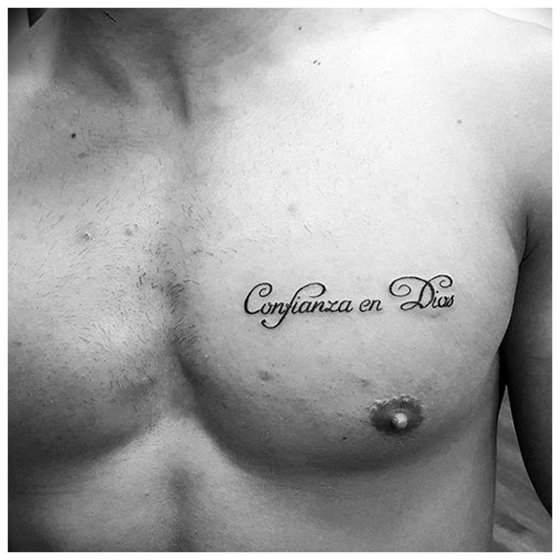 Kleine tattoo-inscriptie op de borst.